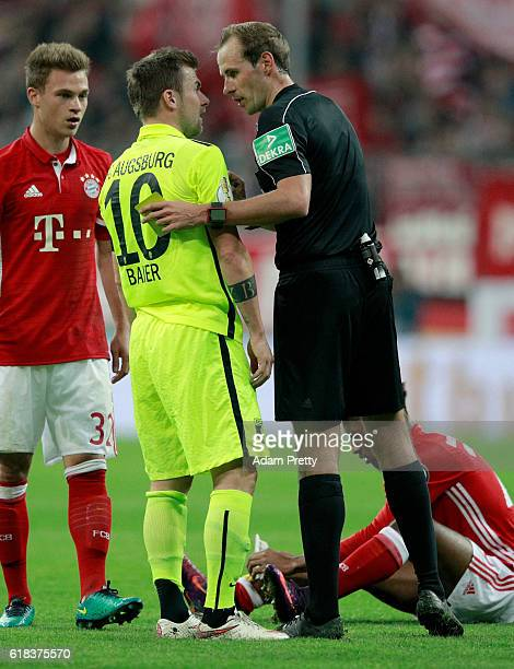 Referee Sascha Stegemann argues with Daniel Baier of Augsburg during the DFB Cup second round match between Bayern Muenchen and FC Augsburg at...