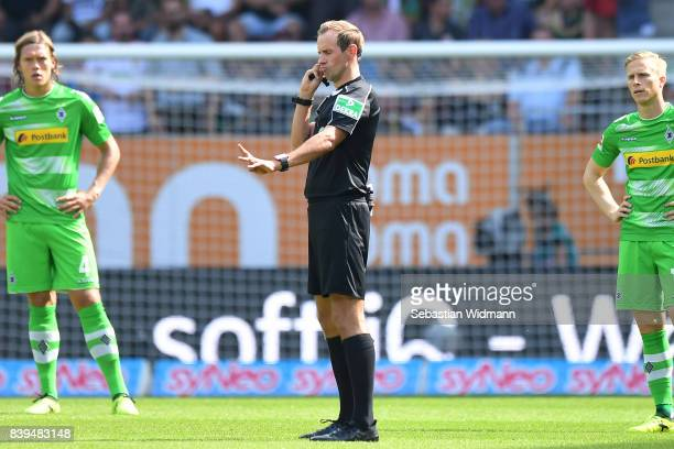 Referee Sascha Stegemann checks with the video referee if the first goal was correct during the Bundesliga match between FC Augsburg and Borussia...