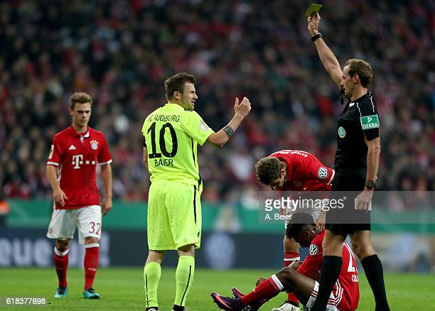 Referee Sascha Stegemann shows Daniel Baier of Augsburg the yellow card during the DFB Cup second round match between Bayern Muenchen and FC Augsburg...