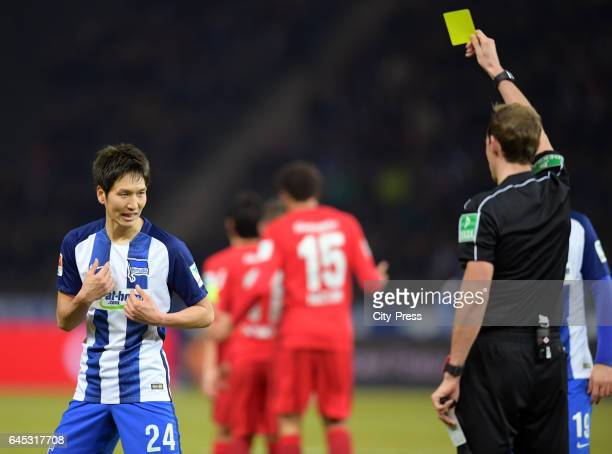referee Sascha Stegemann shows Genki Haraguchi of Hertha BSC the yellow card during the game between Hertha BSC and the Eintracht Frankfurt on...