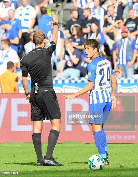 referee Sascha Stegemann shows Genki Haraguchi of Hertha BSC the yellow card during the game between Hertha BSC and dem VfB Stuttgart on August 19...