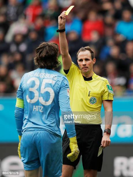 Referee Sascha Stegemann shows Marwin Hitz of Augsburg a yellow card which resulted in a penalty goal during the Bundesliga match between FC Augsburg...