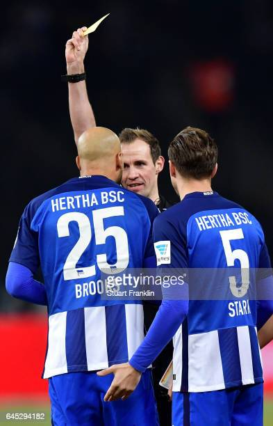 Referee Sascha Stegemann shows the yellow card to John Brooks of Berlin during the Bundesliga match between Hertha BSC and Eintracht Frankfurt at...