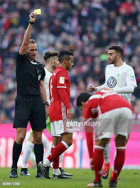Referee Sascha Stegemann shows the yellow card to Thiago Alcantara of Muenchen during the Bundesliga match between Bayern Muenchen and VfL Wolfsburg...