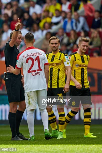 Referee Sascha Stegemann speak with Dominik Kohr of Augsburg during the Bundesliga match between FC Augsburg and Borussia Dortmund at the WWKArena on...