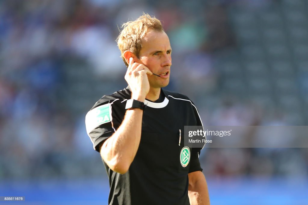 Referee Sascha Stegermann listen to the video referee during the Bundesliga match between Hertha BSC and VfB Stuttgart at Olympiastadion on August 19, 2017 in Berlin, Germany.