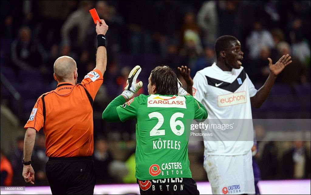Referee Sebastien Delferiere shows a red card to Kara Mbodjii Serigne of GENK during the Cofidis Cup match between RSC Anderlecht and KRC Genk on January 30, 2013 in Anderlecht, Belgium.