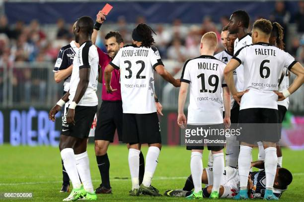 Referee Sebastien Desiage shows a red card to Benoit Assou Ekotto of Metz as Adam Ounas of Bordeaux lays down after being injured during the Ligue 1...