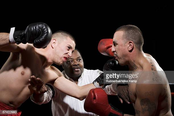 Referee separating two boxers during a fight