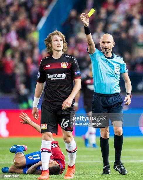 Referee Sergei Karasev shows Tin Jedvaj of Bayer 04 Leverkusen a yellow card during their 201617 UEFA Champions League Round of 16 second leg match...