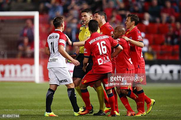 Referee Shaun Evans holds back Brendon Santalab of the Wanderers from Adelaide players after he made a hard tackle on James Holland of Adelaide...