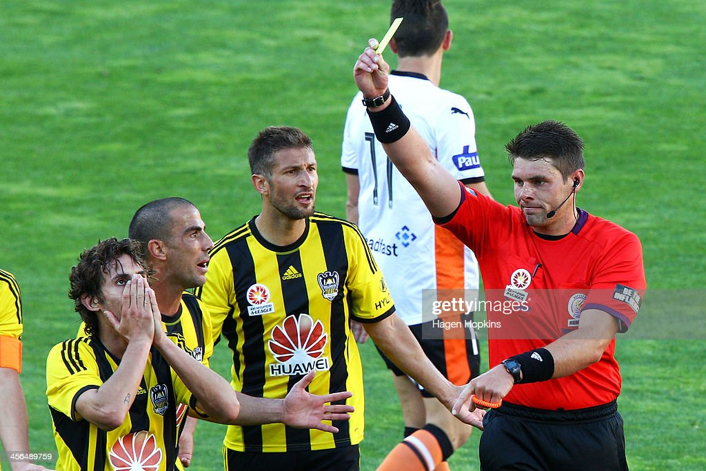 Referee Shaun Evans shows a yellow card to <a gi-track='captionPersonalityLinkClicked' href=/galleries/search?phrase=Albert+Riera&family=editorial&specificpeople=657194 ng-click='$event.stopPropagation()'>Albert Riera</a> (L) of the Phoenix while teammates Manny Muscat and Vince Lia question the call during the round 10 A-League match between the Wellington Phoenix and Brisbane Roar at Westpac Stadium on December 14, 2013 in Wellington, New Zealand.