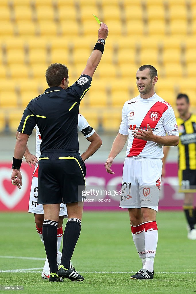 Referee Shaun Evans shows Steven Gray (R) of the Heart a yellow card during the round 13 A-League match between the Wellington Phoenix and the Melbourne Heart at Westpac Stadium on December 27, 2012 in Wellington, New Zealand.