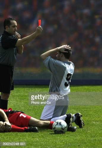 Referee showing football player red card : Stock Photo