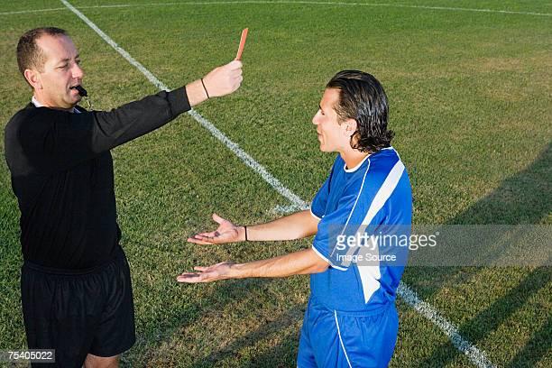 Schiedsrichter die rote Karte zeigen Fußballer