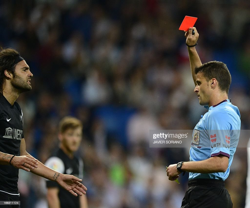 Referee (R) shows a red car to Malaga's defender Sergio Sanchez during the Spanish league football match Real Madrid CF vs Malaga CF at the Santiago Bernabeu stadium in Madrid on May 8, 2013. AFP PHOTO/ JAVIER SORIANO