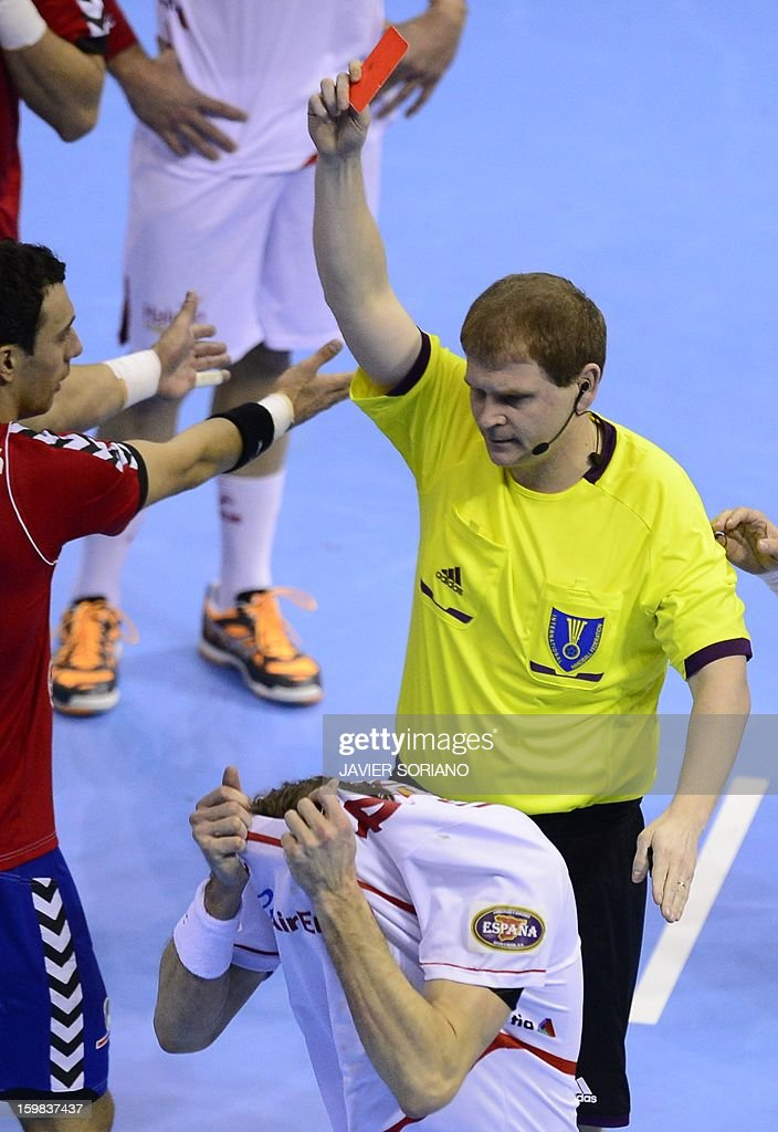 Referee shows a red car to Spain's left back Viran Morros (C) during the 23rd Men's Handball World Championships round of 16 match Serbia vs Spain at the Pabellon Principe Felipe in Zaragoza on January 21, 2013. AFP PHOTO/ JAVIER SORIANO
