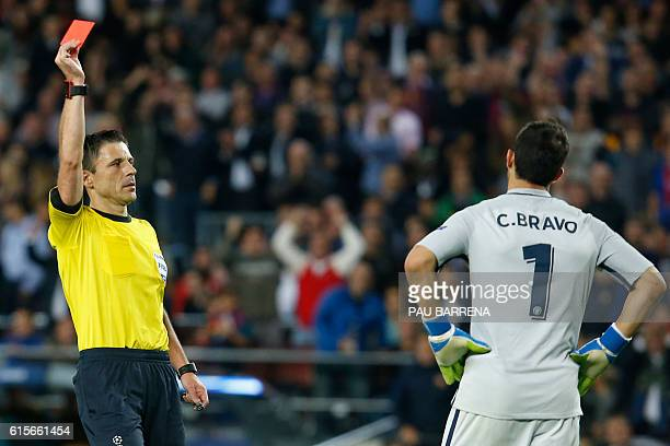 TOPSHOT Referee shows a red card to Manchester City's Chilean goalkeeper Claudio Bravo during the UEFA Champions League football match FC Barcelona...