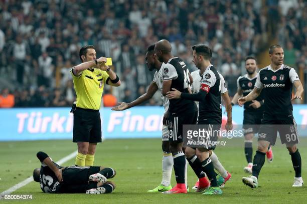 Referee shows a yellow card as Emanuel Emenike of Fenerbahce argues with Cenk Tosun of Besiktas during Turkish Spor Toto Super Lig soccer match...