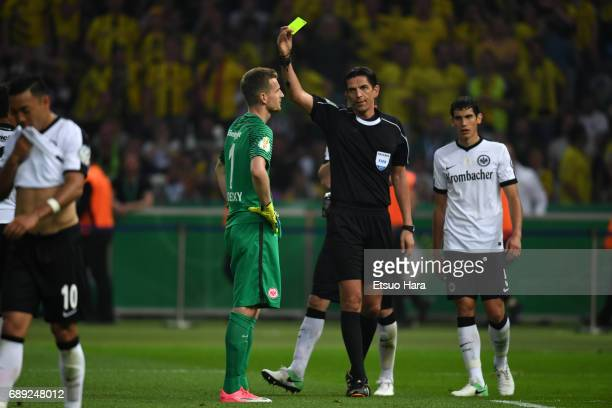 Referee shows an yellow card to Lukas Hradecky of Eintrachat Frankfurt during the DFB Cup Final match between Eintracht Frankfurt and Borussia...