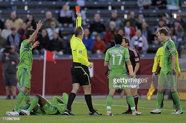 Referee Silviu Petrescu gives a red card to Brian Mullan of the Colorado Rapids for a foul on Steve Zakuani of the Seattle Sounders FC in the third...