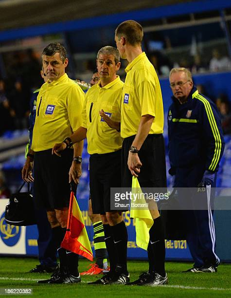 Referee Simon Hooper has words with his assistant referees during the Capital One Cup Fourth Round match between Birmingham City and Stoke City at St...