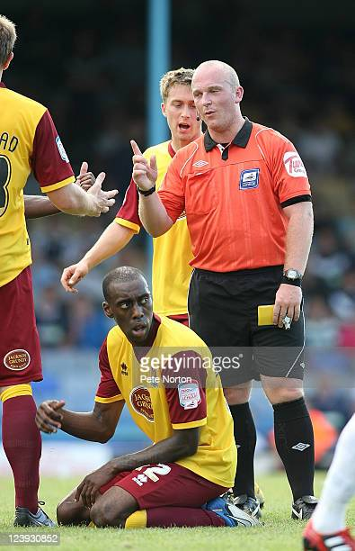 Referee Simon Hooper stands over Nick McKoy of Northampton Town prior to showing him a second yellow card during the npower League Two match between...