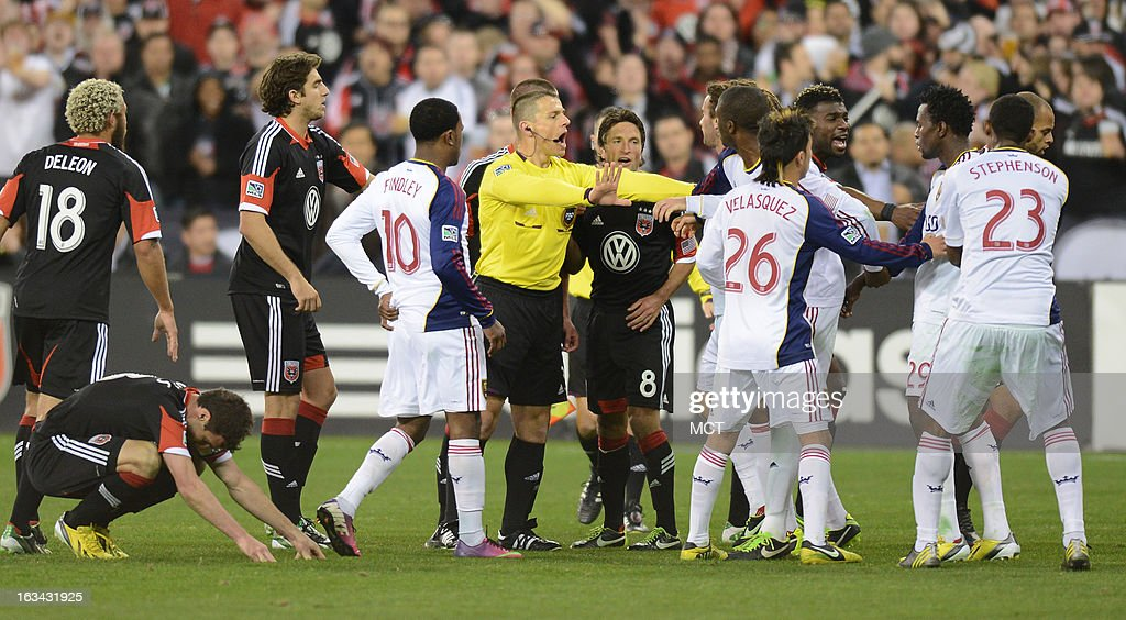 Referee Sorin Stoica, center, separates players after a head-butting incident involving Real Salt Lake defender Kenny Mansally (29) and D.C. United midfielder Perry Kitchen (23) in the second half at RFK Stadium in Washington, D.C., Saturday, March 9, 2013. Kitchen confronted Marsally, after Marsally delivered a hit on D.C. United forward Chris Pontius (13), left, on the pitch. United defeated RSL, 1-0.