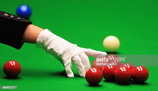 A referee spots a ball during day one of the The Dafabet World Snooker Championship at Crucible Theatre on April 19 2014 in Sheffield England