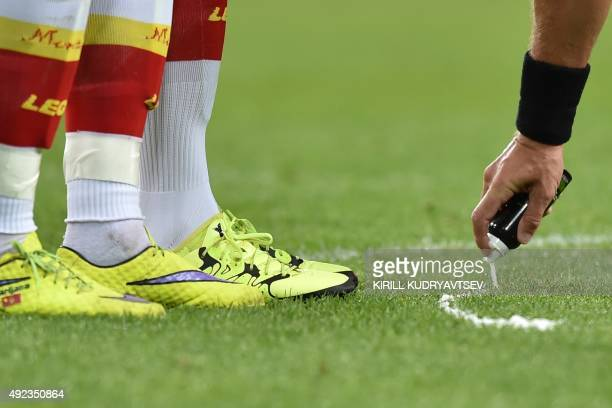 A referee sprays marker on the pitch during the UEFA Euro 2016 group G qualifying football match between Russia and Montenegro at the Otkrytie Arena...