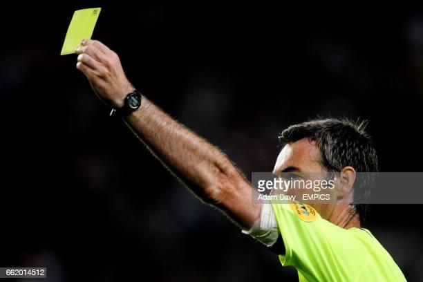 Referee Stefano Farina branishes a yellow card