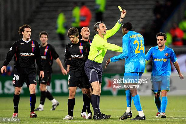 Referee Stefano Farina gives a yellow card during the champions league soccer match between Olympique Lyonnais and FC Barcelona
