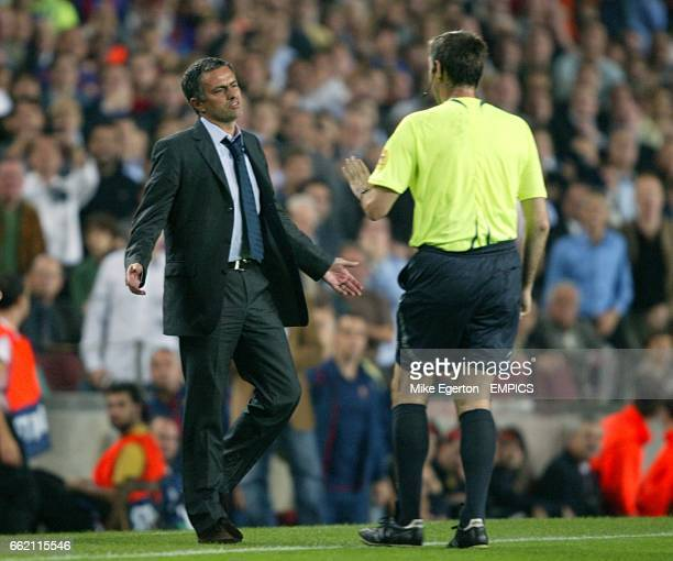 Referee Stefano Farina is confronted by Chelsea manager Jose Mourinho after he booked Ashley Cole