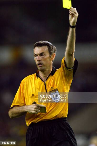 Referee Stefano Farina shows the yellow card to a player