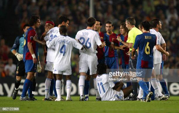 Referee Stefano Farina tries to part the Chelsea and Barcelona players after Didier Drogba went down