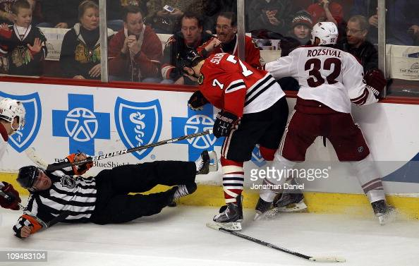 Referee Stephane Auger is knocked to the ice as Brent Seabrook of the Chicago Blackhawks and Michal Rozsival of the Phoenix Coyotes battle for the...
