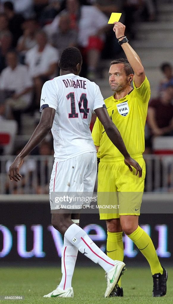 Referee Stephane Lannoy gives a yellow card to Bordeaux's Malian forward Cheick Diabate (L) during the French L1 football match Nice (OGCN) vs Bordeaux (FCGB) on August 23, 2014 at the Allianz Riviera stadium, in Nice, southeastern France.