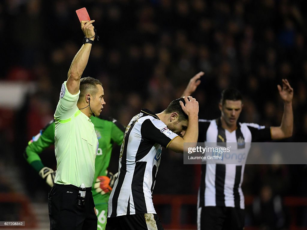 Referee Stephen Martin shows a red card to Paul Dummett of Newcastle United during the Sky Bet Championship match between Nottingham Forest and Newcastle United at City Ground on December 2, 2016 in Nottingham, England.