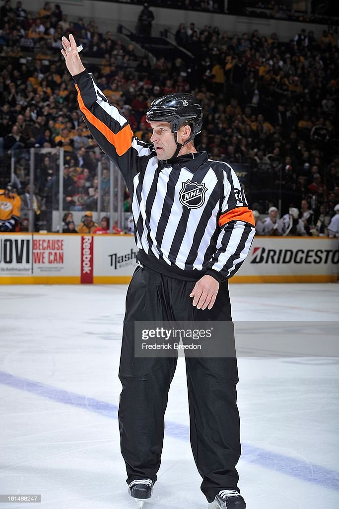 NHL referee Stephen Walkom #24 officiates a game between the Nashville Predators and the Chicago Blackhawks at the Bridgestone Arena on February 10, 2013 in Nashville, Tennessee.