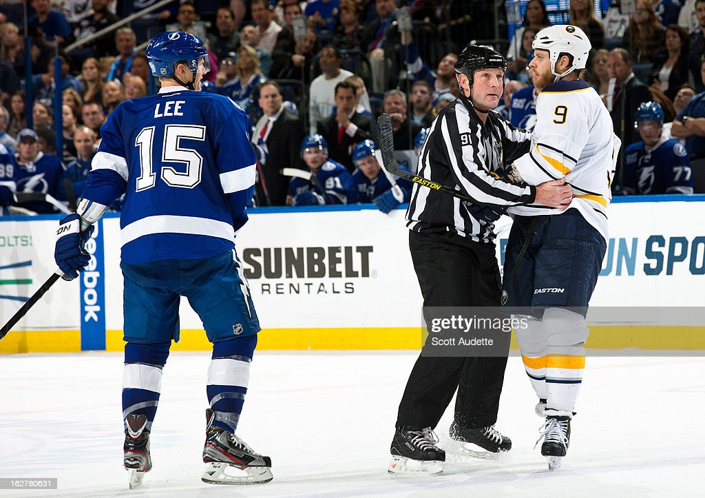 A referee steps in between Brian Lee #15 of the Tampa Bay Lightning and Steve Ott #9 Buffalo Sabres during the second period of the game at the Tampa Bay Times Forum on February 26, 2013 in Tampa, Florida.