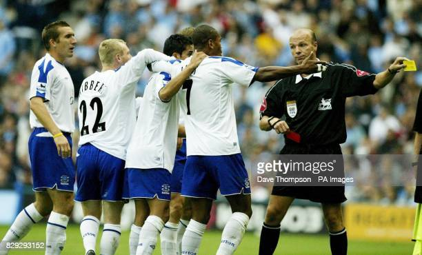 Referee Steve Bennett sends off Everton's Tim Cahill after the player pulled his shirt over his head in celebration after scoring against Manchester...