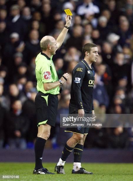 Referee Steve Bennett shows Portsmouth's Sean Davis a yellow card after a challnege on Tottenham Hotspur's Roman Pavlyuchenko