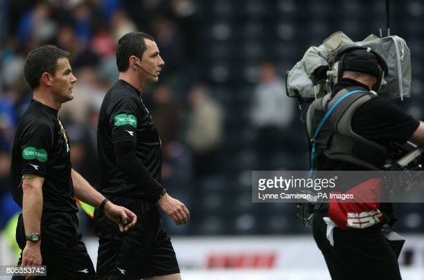Referee Steve Conroy leaves the pitch under the spotlight of the TV camera