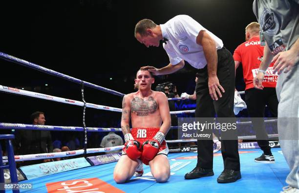 Referee Steve Gray consoles Robbie Barrett after he is stopped with a technical knock out against Lewis Ritson during the British Lightweight...