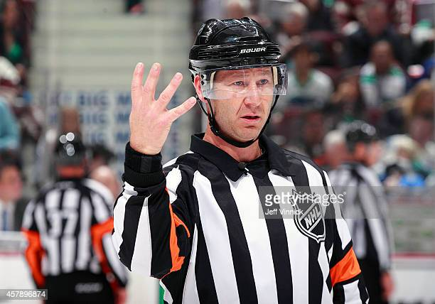 Referee Steve Kozari makes a call during the NHL game between the Vancouver Canucks and the Tampa Bay Lightning at Rogers Arena October 18 2014 in...
