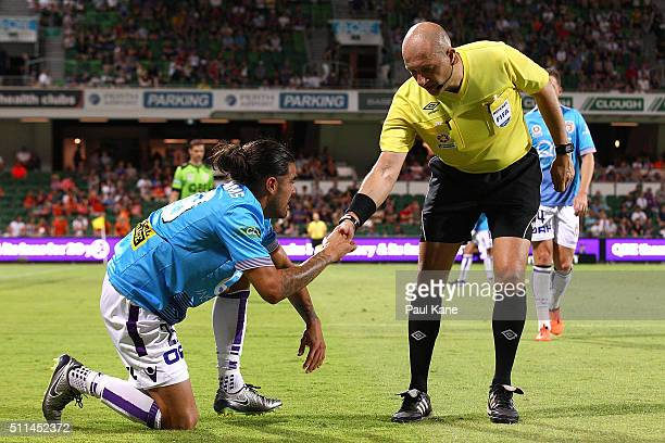 Referee Strebre Delovski assists Aryn Williams of the Glory to his feet during the round 20 ALeague match between the Perth Glory and Brisbane Roar...