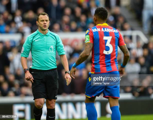 Referee Stuart Attwell calls over Patrick Van Aanholt of Crystal Palace to receive a yellow card during the Premier League match between Newcastle...