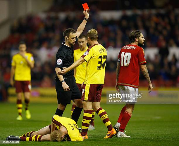 Referee Stuart Attwell sends off Henri Lansbury of Nottingham Forest during the Sky Bet Championship match between Nottingham Forest and Burnley at...