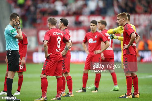 Referee Sven Jablonski listens to the video assistant referee in his headset before taking back a goal of Kevin Volland of Leverkusen during the...