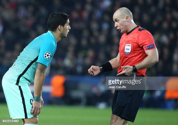 Referee Szymon Marciniak of Poland warns Luis Suarez of FC Barcelona during the UEFA Champions League Round of 16 first leg match between Paris...